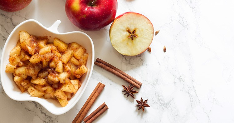 Apples, cinnamon and chunky applesauce on white background
